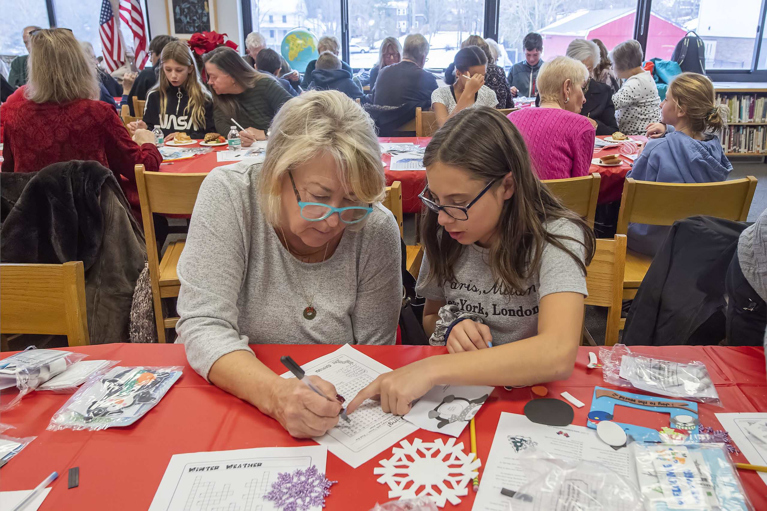 Hailey Bierfriend works on a word puzzle with her Step-Grandmother Nancy Buckley during the Pierson Middle School Snowflake Tea that was held in the Pierson High School library on Friday , December 13.     MICHAEL HELLER PHOTO