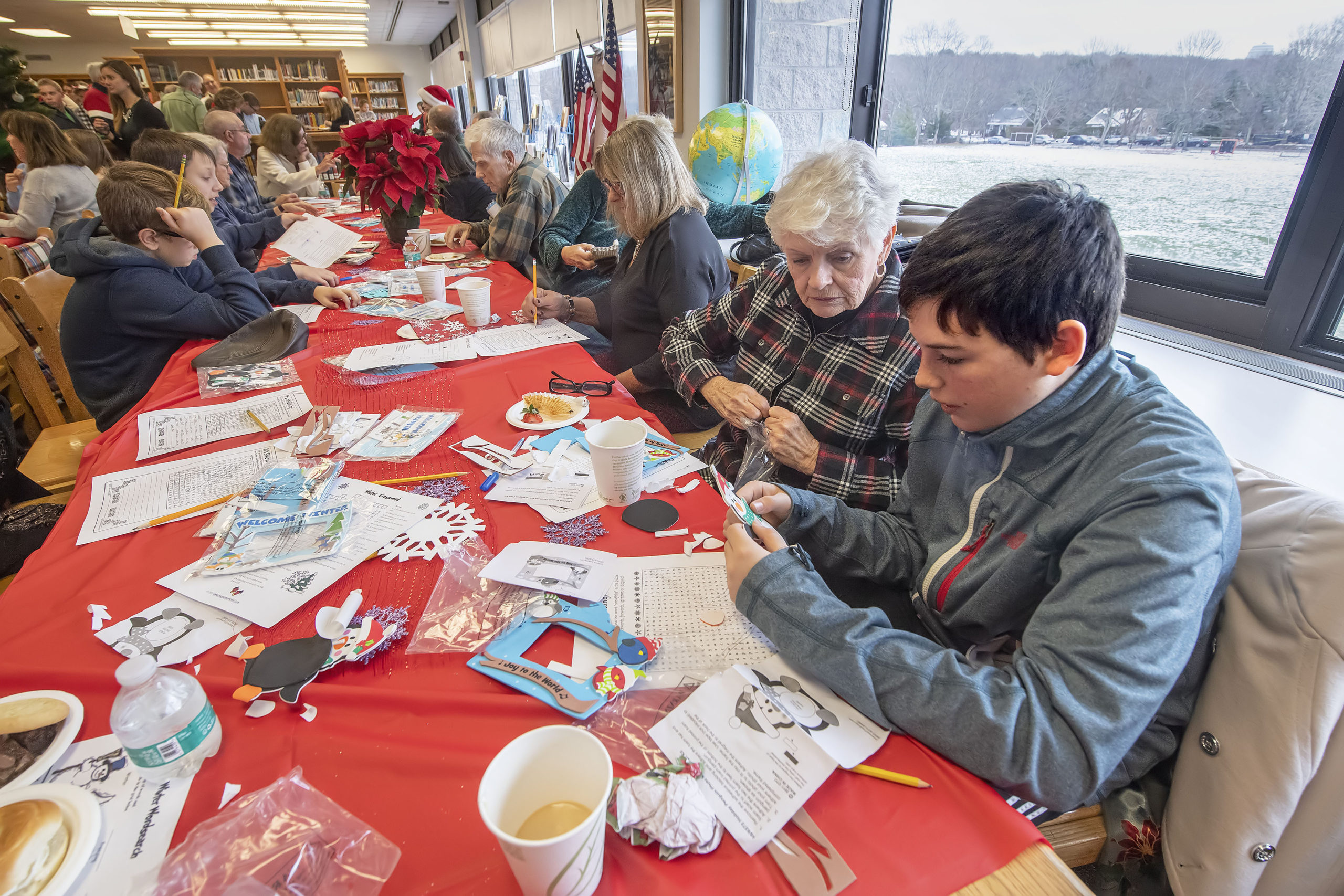 Patrick Caufield works on making a picture frame with his grandmother Gerri during the Pierson Middle School Snowflake Tea that was held in the Pierson High School library on Friday, December 13.   MICHAEL HELLER