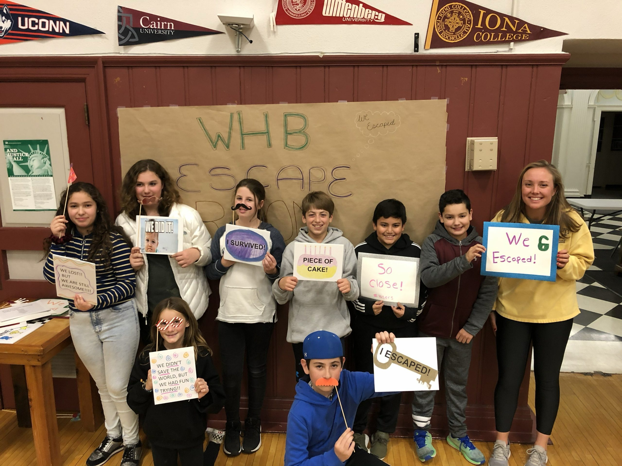 """Eighth-graders in Kelly Russell's critical literacy class at Westhampton Beach Middle School gave back to the district's Hurricane Foundation by organizing an escape room fundraiser on December 3. The inspiration for the event began in seventh grade, when the students learned about the United Nations Messengers of Peace program as part of their curriculum. Expanding on the lesson this year, they decided to organize a fundraiser for which they designed an escape room around the theme of """"evil science lab."""" Participants were given clues and moved through 10 rooms to solve riddles, find a blueprint and race back to the school's cafeteria to crack the final code. The event also included a student-run bake sale and a photo booth featuring various props, ultimately raising more than $800."""