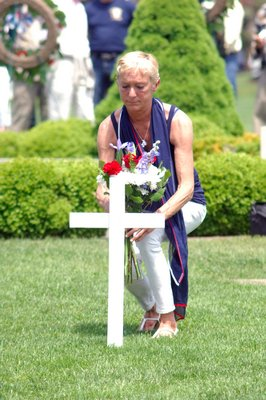 Lisa Frankenbach places flowers at services in Agawam Park on Monday.  DANA SHAW