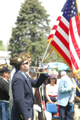 Kevin McMahon plays Taps at Memorial Day services in Southampton Village on Monday.  DANA SHAW