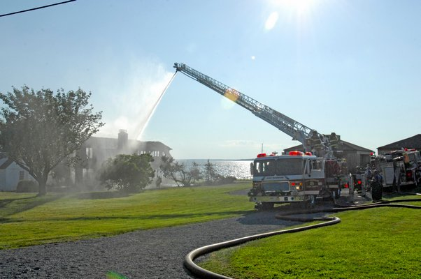 Firefighters work to put out a stucture fire in Noyac on Thursday afternoon.  DANA SHAW