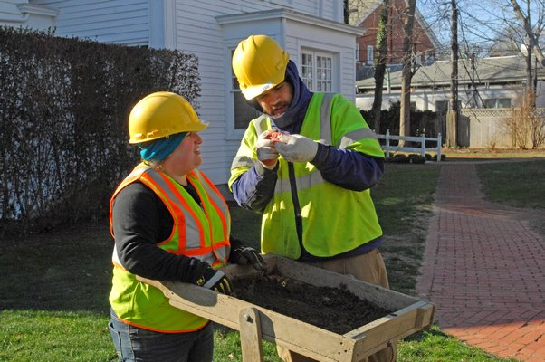 Archaeological Field Technicians Sara Regensburger and Douglas Boucher of the Louis Berger Group examine an item found on the grounds of the Rogers Mansion in Southampton Village.  DANA SHAW