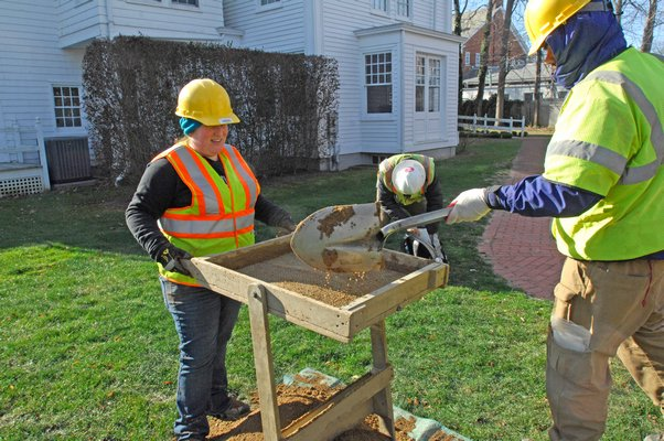 Archaeological Field Technicians Sara Regensburger and Douglas Boucher of the Louis Berger Group dig and sift through soil at the Rogers Mansion on Wednesday.  DANA SHAW