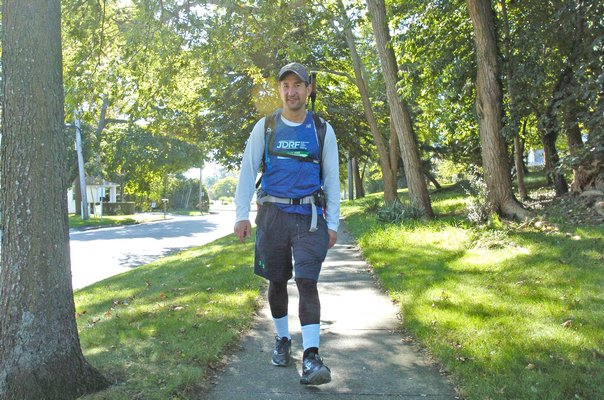 Michael Ehrlich walks through Southampton Viallge on his way to Montauk on Wednesday. DANA SHAW