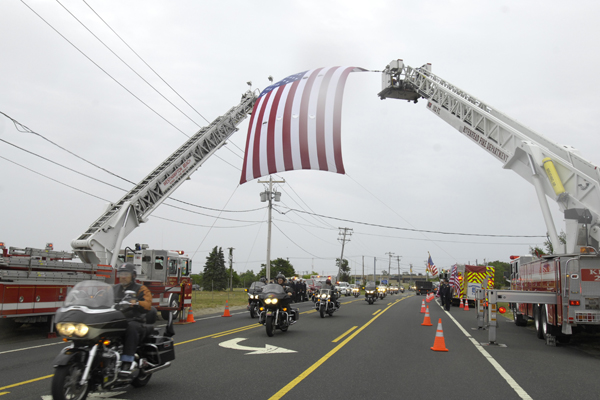 underneath an American flag hanged over the road by the Southampton Fire Department.<br></noscript>Photo by Brendan O'Reilly