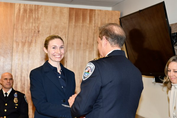 Officer Caryl Pfeiffer shakes Southampton Town Police Chief Steven Skyrnecki's hand after being sworn in.