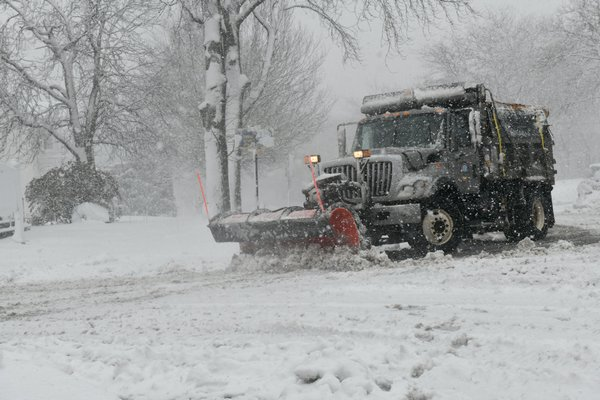 Crews in Southampton Village work to clear roads as a steady snow falls on Tuesday morning.  DANA SHAW