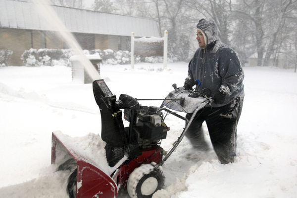 Jim O'Connell clears snow early on Wednesday morning in Hampton Bays.   DANA SHAW