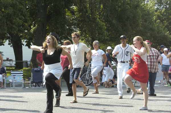 """A  flashmob of costumed actors burst into song and dance at the intersection of Main Street and Jobs Lane in an effort to promote their upcoming production of """"Working"""