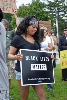 Organizer Vanessa Vascez-Corleone holds a Black Lives Matter sign during a rally in Westhampton Beach on Sunday. AMANDA BERNOCCO