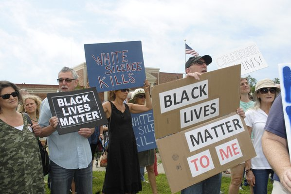 Participants hold signs during a Black Lives Matter rally in Westhampton Beach on Sunday. AMANDA BERNOCCO