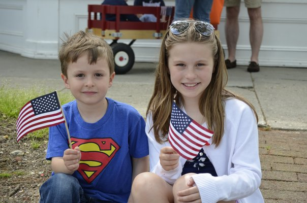 Sofia and Robert Elder wave American flags during the Memorial Day Parade in Southampton VIllage on Monday. BY ERIN MCKINLEY
