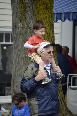 Three-year-old Chase Miller gets a good seat on Michael Miller for the Southampton Village Memorial Day Parade on Monday. BY ERIN MCKINLEY