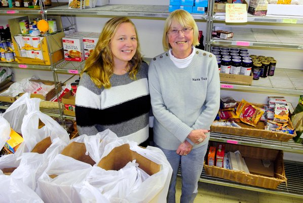 Mary Ann Tupper and Kerry Lewendoski in the food pantry at Human Resources of the Hamptons.  DANA SHAW