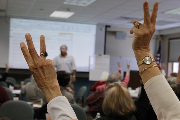 Participants raise their fingers in the air to cast votes for which proposed library improvements should be prioritized if the library board were to float a bond. KYLE CAMPBELL