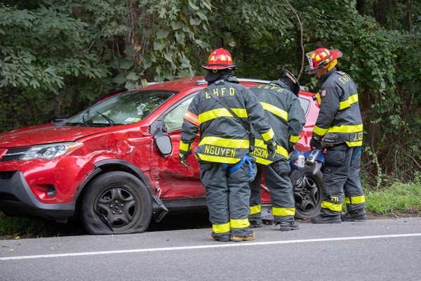 """East Hampton Fire Department members of the """"White Knights"""" rescue company used a hydraulic tool to free a driver from her car who was involved in a fatal motor vehicle accident on Springs-Fireplace Road on Sunday morning.     COURTESY MICHAEL HELLER"""