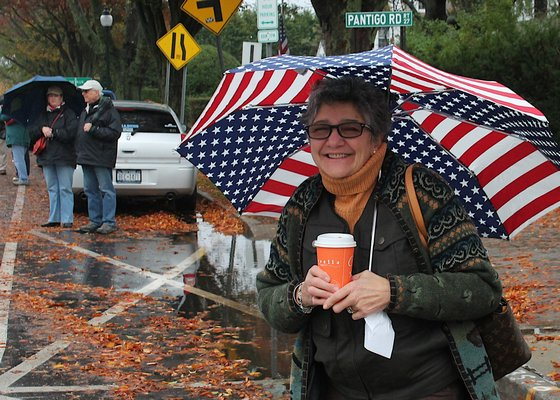 Carole Campolo keeps dry under an umbrella while watching the parade. KYRIL BROMLEY
