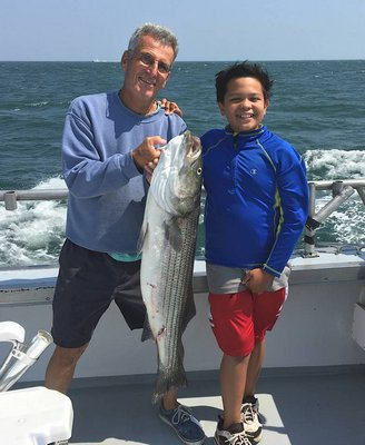 Kyril Bromley and his grandson Ethan show off a 25-pound striper they caught aboard the Montauk charter boat Elizabeth II over the weekend.