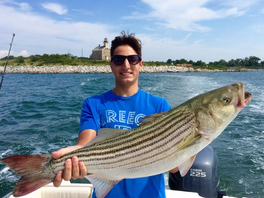 Andrew Stamboulidis with a nice striped bass caught at Plum Island this week. George Stamboulidis