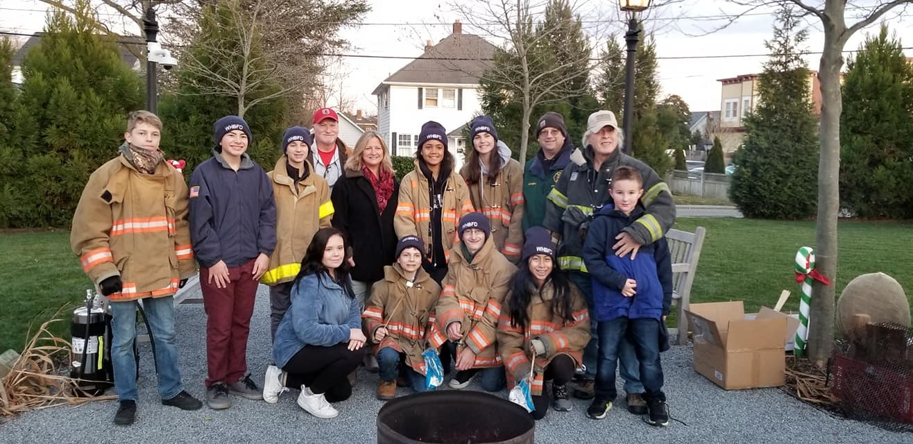 The Westhampton Beach Fire Department Juniors helped out at the Winter Festival on Saturday, December 7 by assisting young children with roasting marshmallows over an open fire and other activities. From left, Eoughan Hayward, Connor Puch, Carter Padavan, Steve Frano, Village Mayor Maria Moore, Zoe Stokes, Makayla Messina, Advisor Chris Kampher, Advisor Paul Hoyle, Evan Hoyle, Natalie Runowski, Finnegan Hayward, Jayson Kampher and Michelle Castro.