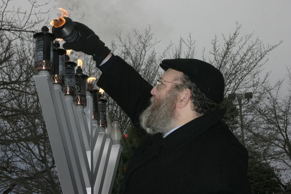 Rabbi Leibel Baumgarten of the Chabad Lubavitch of the Hamptons lights the menorah candles in Herrick Park on Sunday. MICHAEL WRIGHT