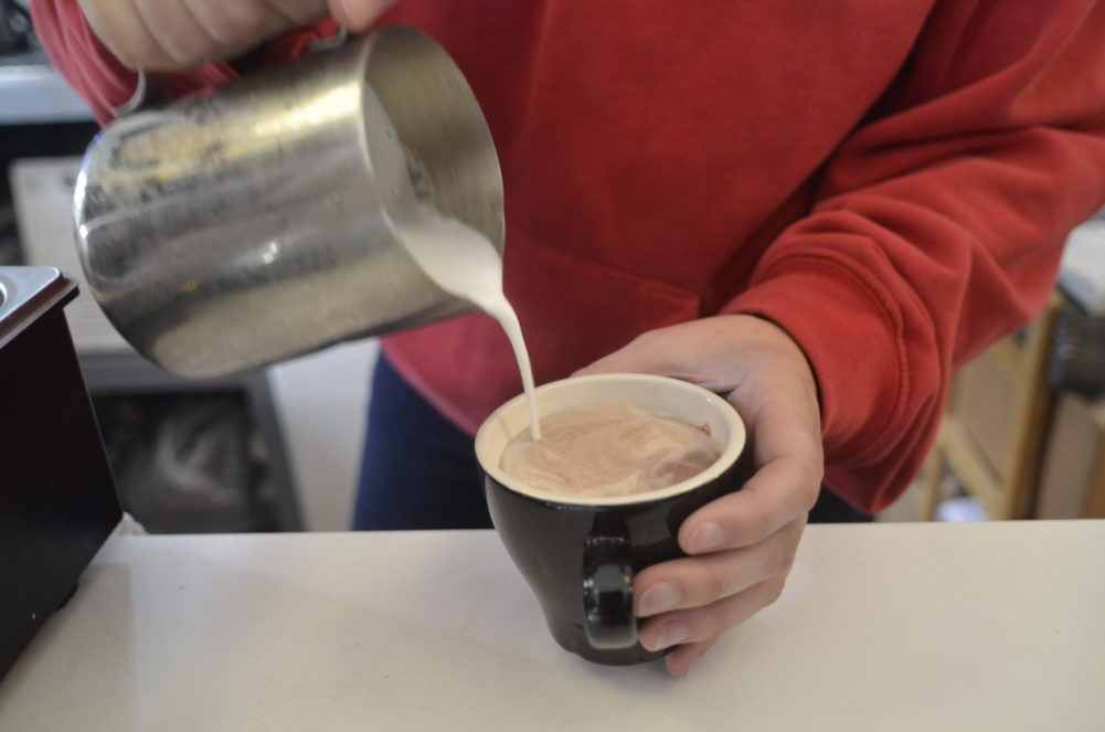 Pouring milk into hot chocolate. KIM COVELL