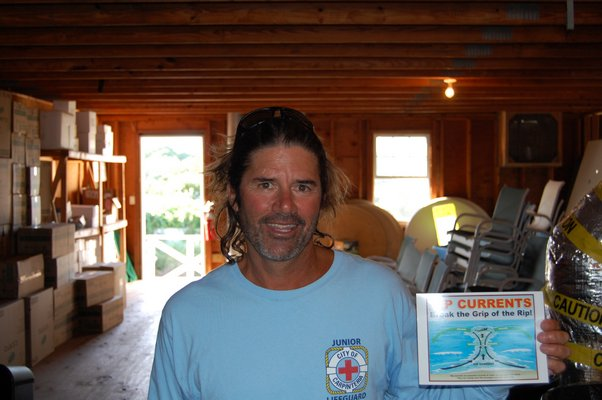 Jimmy Minardi showing one of the many signs he designed detailing how to avoid rip currents JON WINKLER