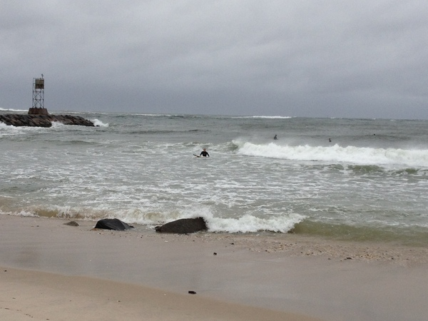 Surfers at the Shinnecock Inlet on Sunday morning. DANA SHAW