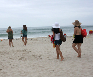 Extras walk onto Rogers Beach to film an online game for USA Network's Royal Pains