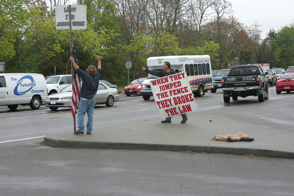 Tom Wedell and George John Van Overbeck protest illegal immigration in front of 7-Eleven in Southampton Village. On Friday morning Latino immigrants staged a brief counter-protest.