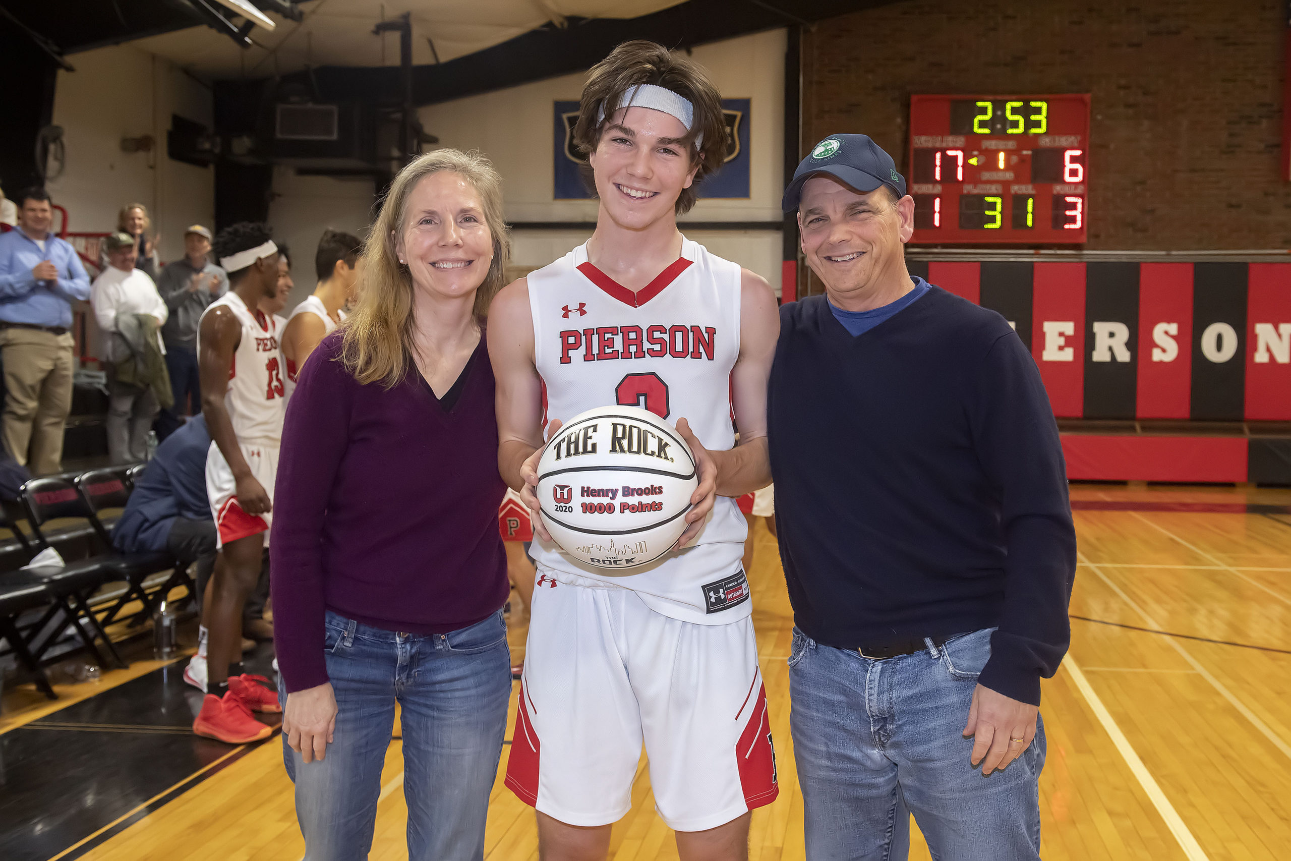 Pierson's Henry Brooks with his parents, Margaret and Scott, after he made his 1,000th career point on Monday night.