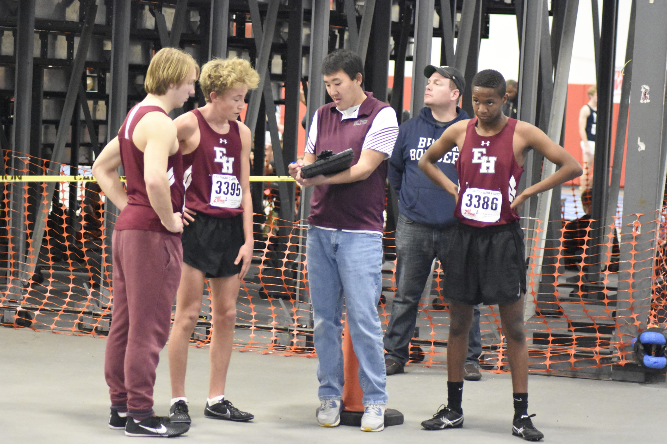East Hampton head coach Ben Turnbull goes over a few things with Ben McErlean and his other athletes.