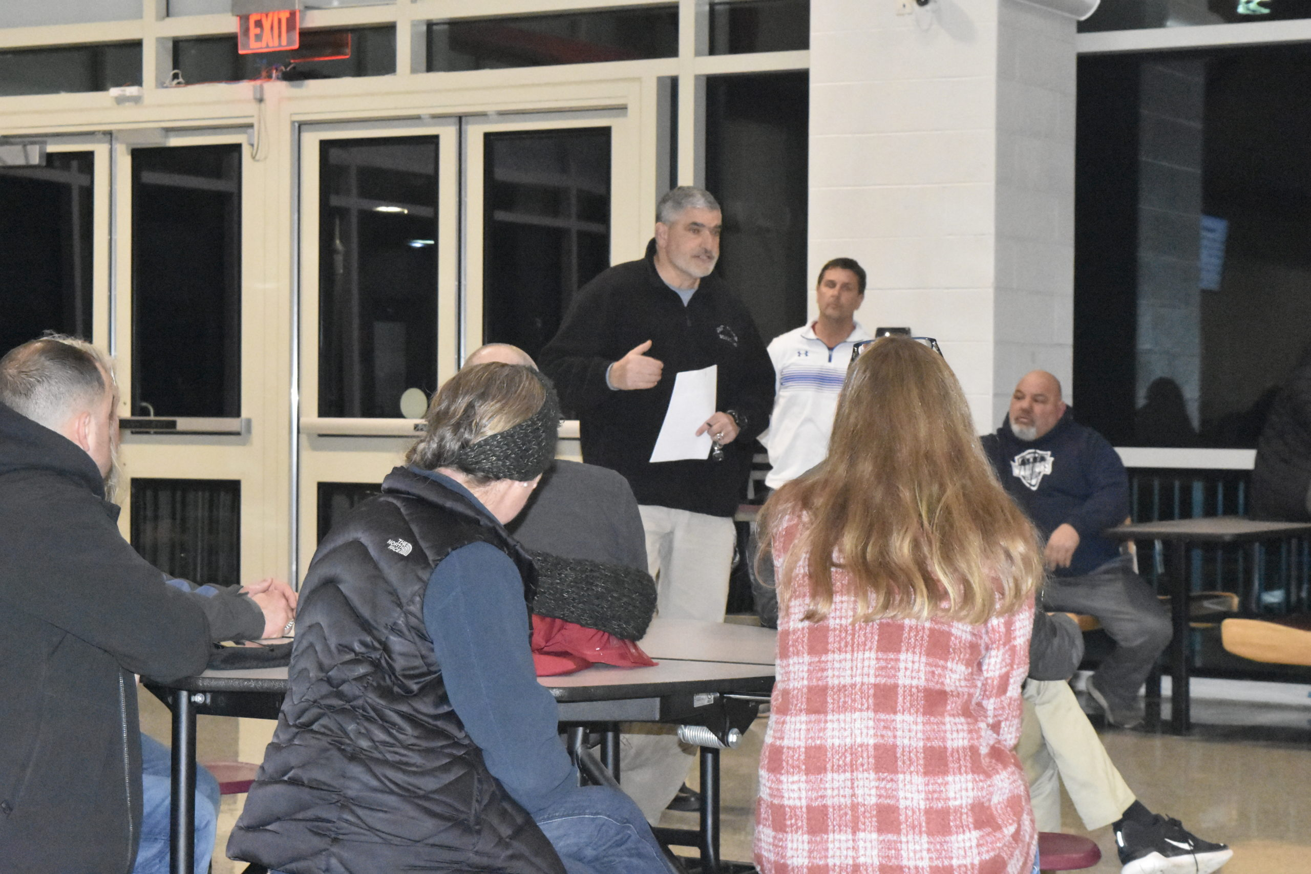 East Hampton Athletic Director Joe Vasile-Cozzo talks with parents and players during a football meeting on Thursday, January 9.
