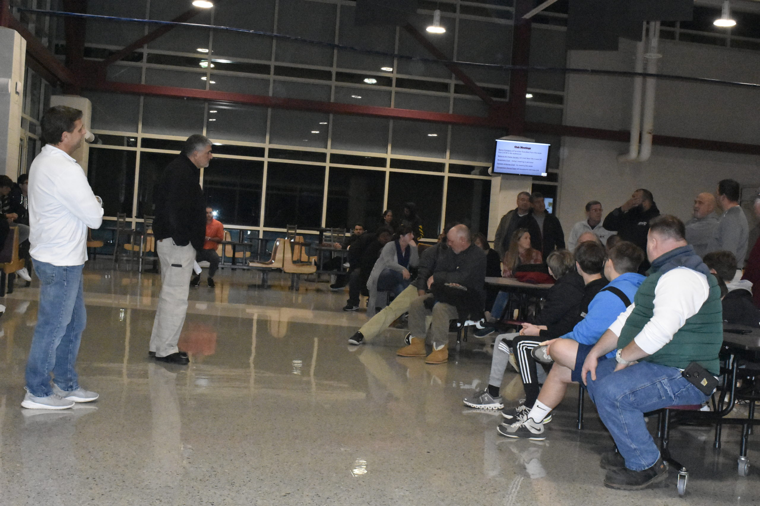 East Hampton Athletic Director Joe Vasile-Cozzo and Southampton Athletic Director Darren Phillips talk with parents and players during a football meeting on Thursday, January 9.
