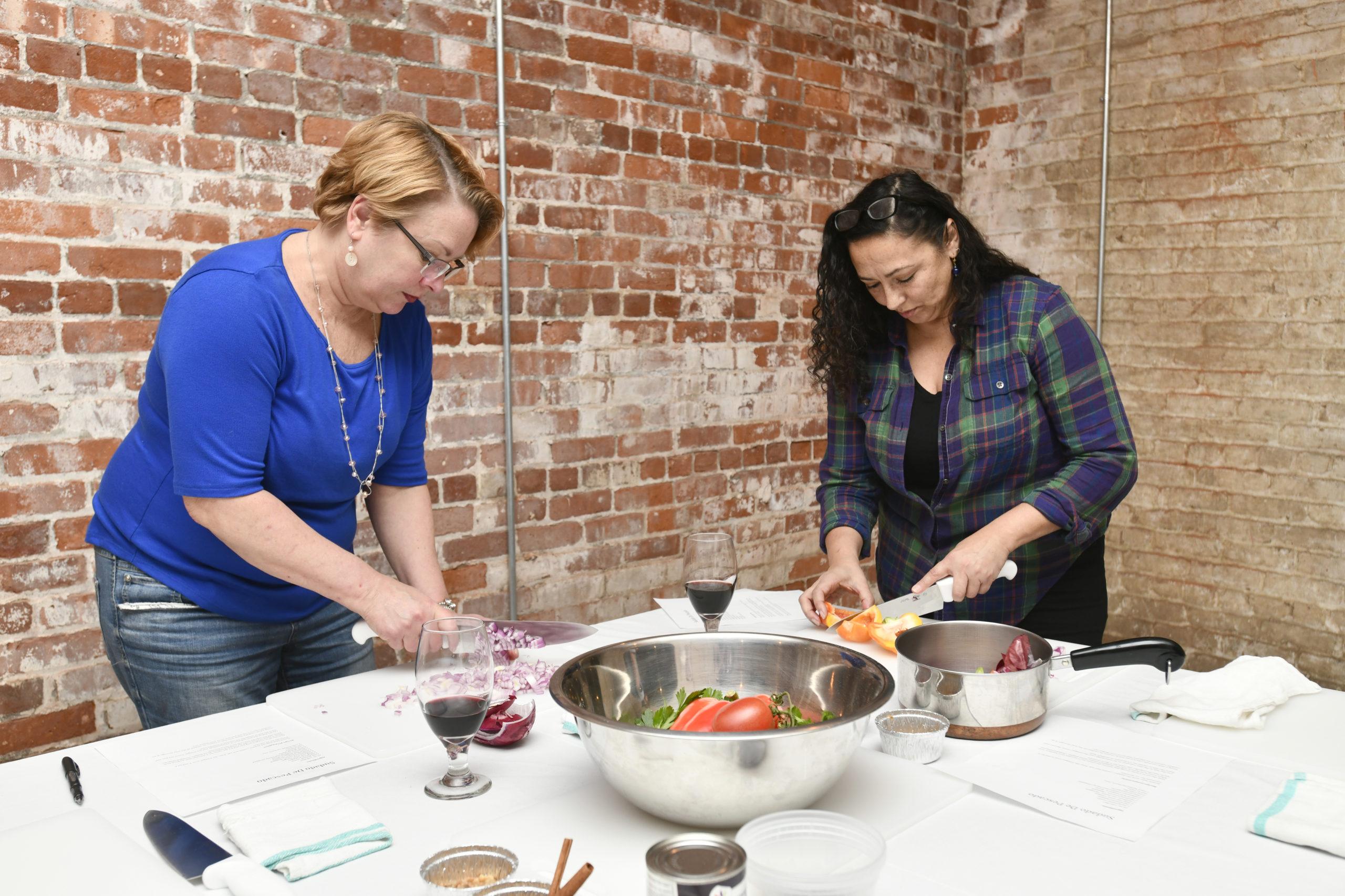 Students Lisa Westfall and Marilyn Cruz chop vegetables.