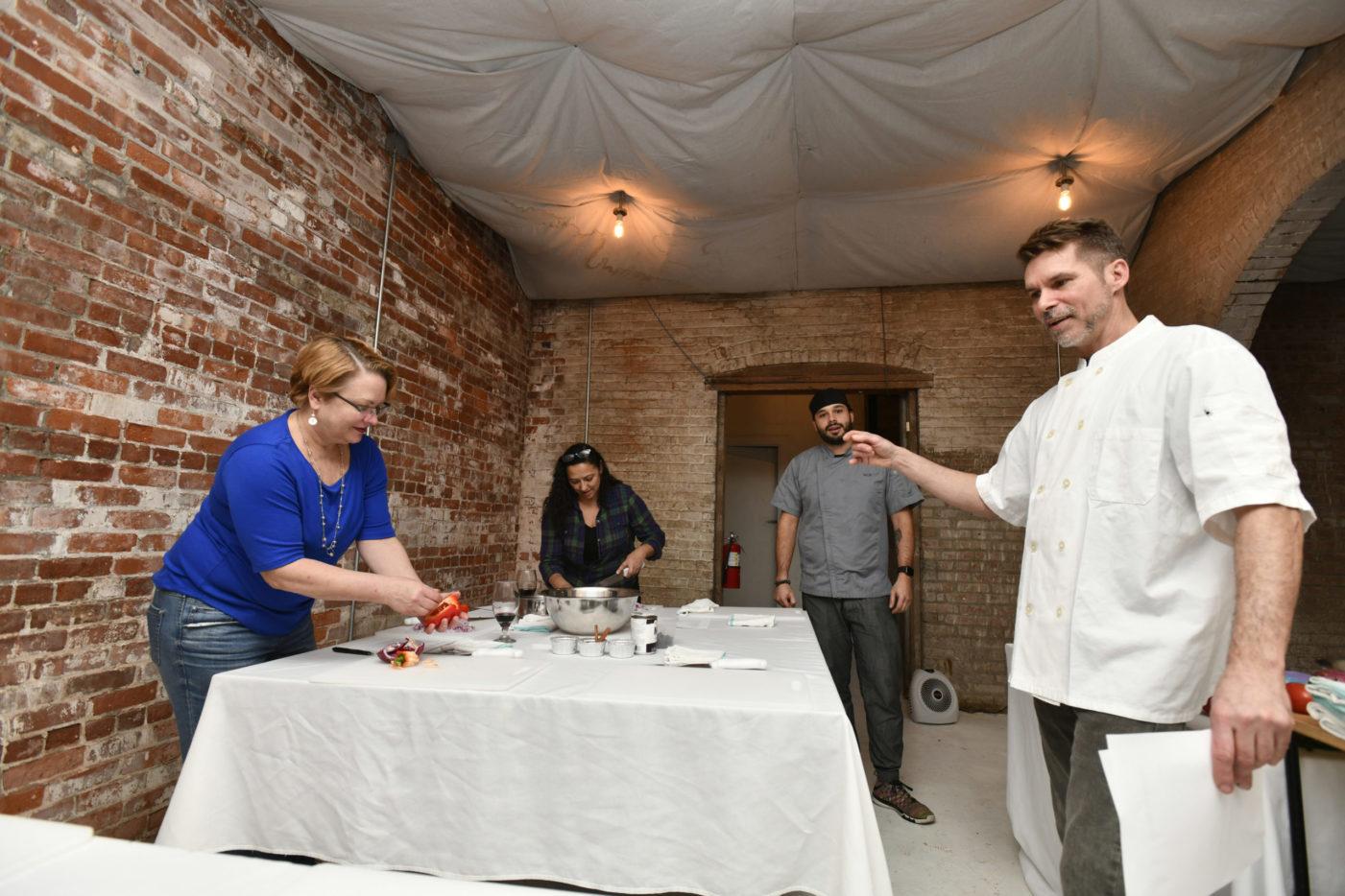 Chefs Nicolas Reisini and Jon Albrecht work with students Lisa Westfall and Marilyn Cruz.