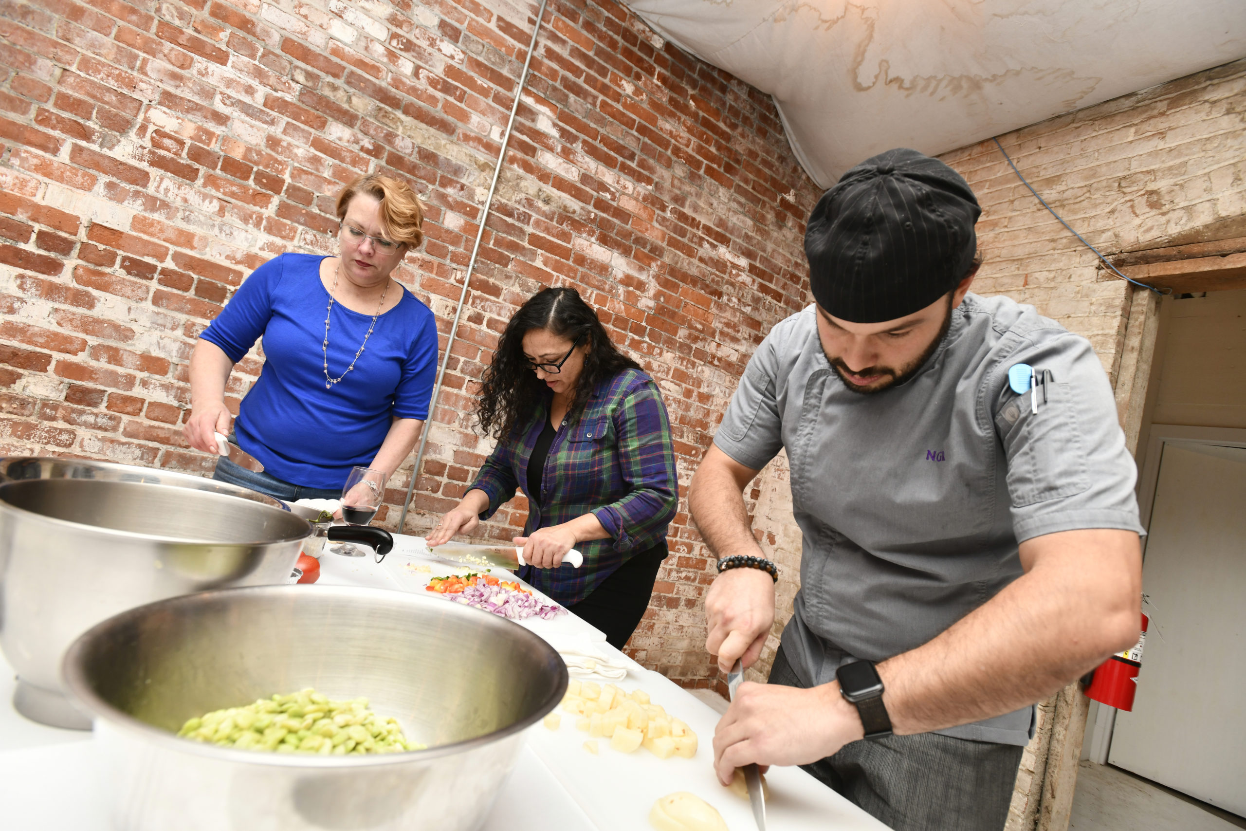 Chef Nicolas Reisini, forground, works with students Lisa Westfall and Marilyn Cruz.