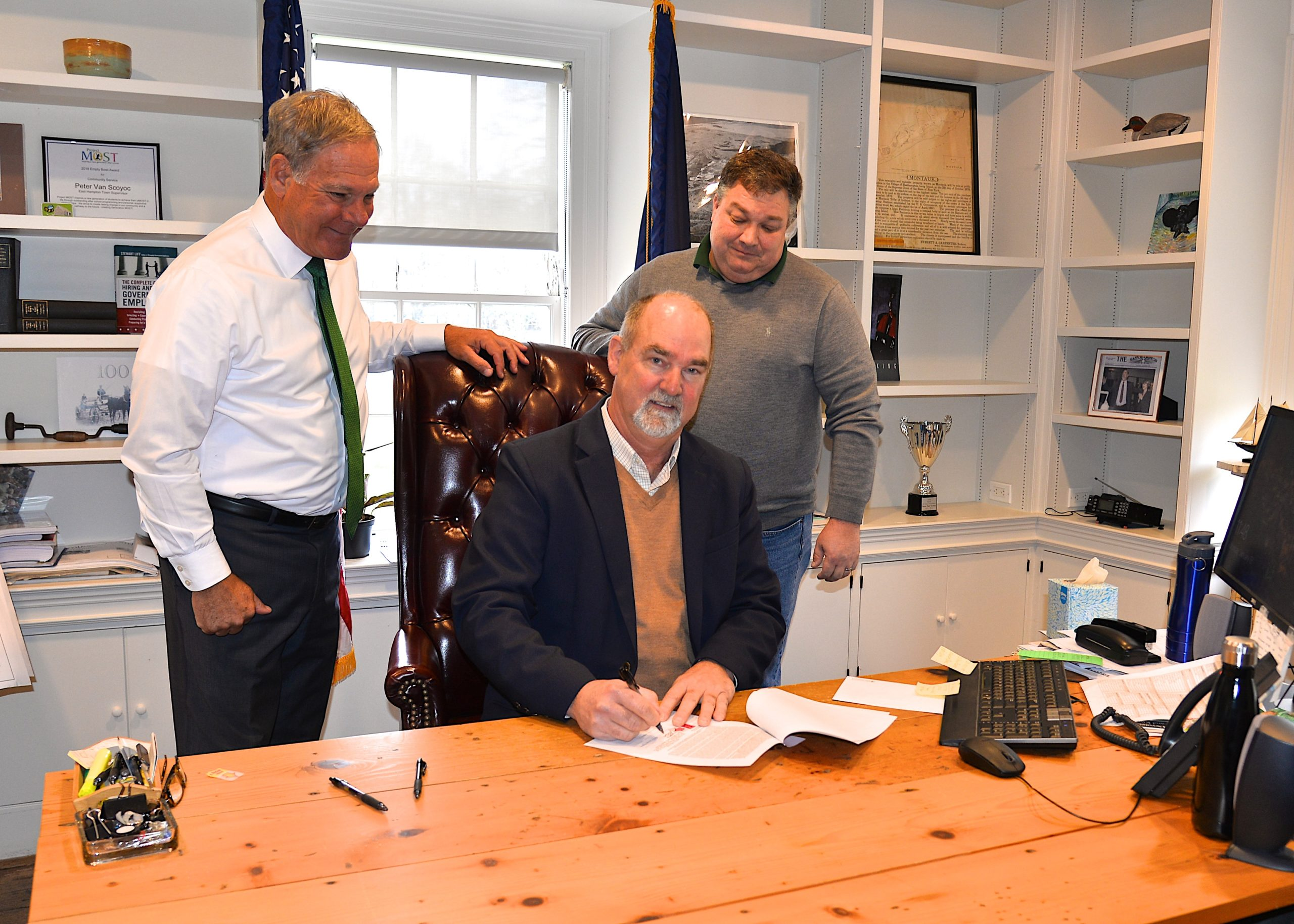 East Hampton Superintendent of Schools Richard Burns. town Supervisor Peter Van Scoyoc, and School Board President J.P., from left to right, met in the supervisor's office Monday to close on the sale of the former scavenger waste treatment site from the town to the school district. The schools will use the property as a bus depot with a classroom for an auto mechanics program. KYRIL BROMLEY