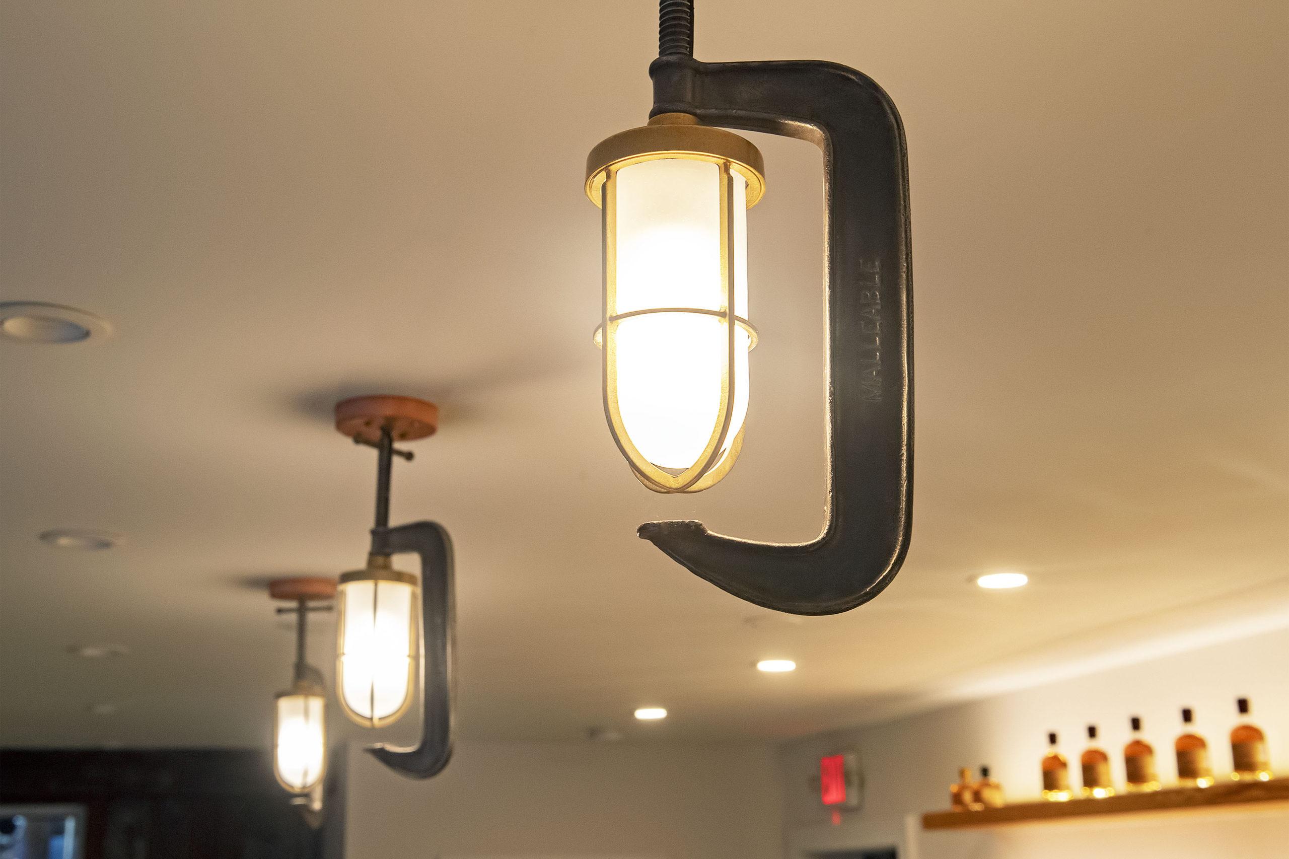 Repurposed clamps create lighting in the tasting room. MICHAEL HELLER