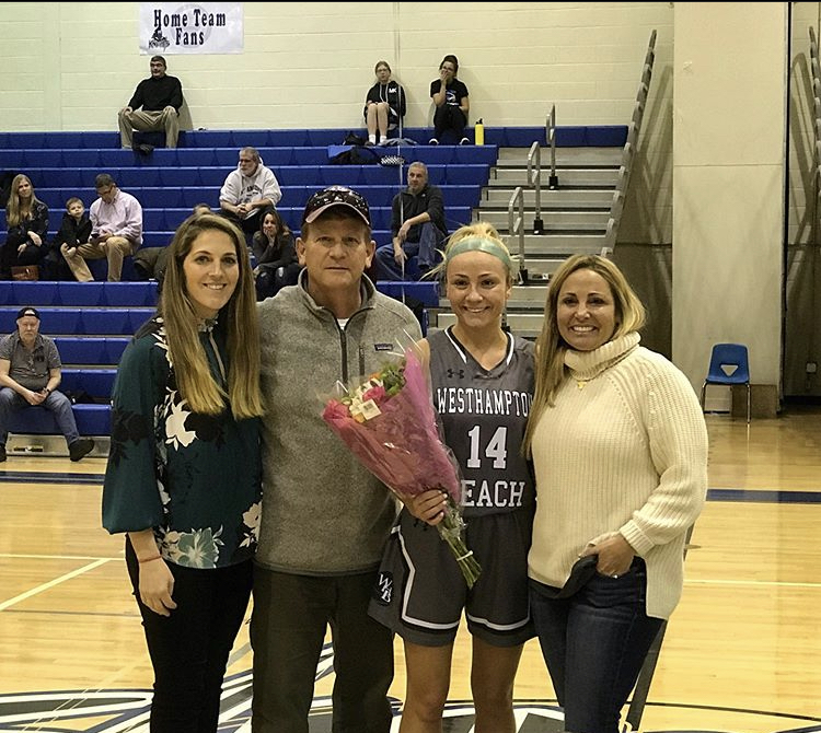 Isabelle Smith with her parents, Tom and Jennifer, and head coach Katie Peters, after scoring her 1,500th career point at Elwood/John Glenn on Monday night.