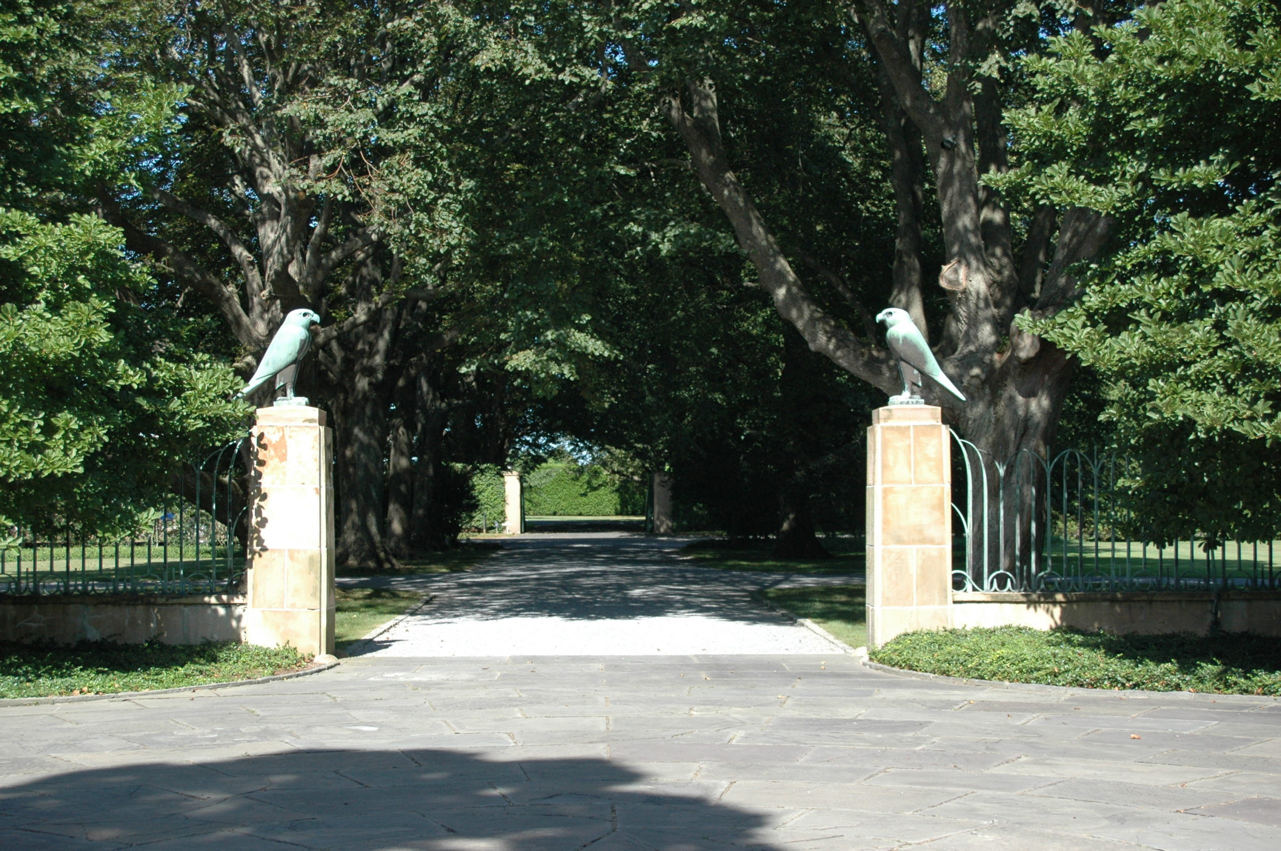 Looking toward Halsey Neck Lane from courtyard with bronze falcons on crab orchard pillars attached to bronze fence  ANNE SURCHIN