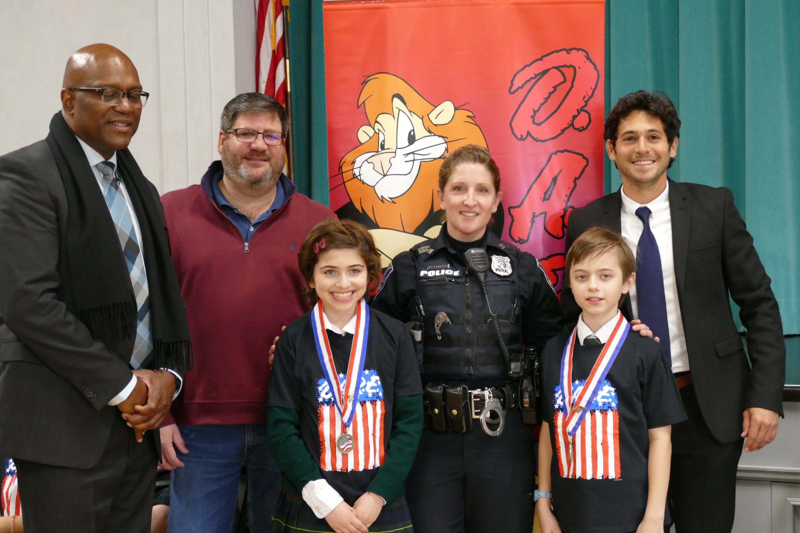 Southampton Police Officer Tiffany Lubold presented Our Lady of the Hamptons School fifth-graders with certificates of completion at the DARE graduation on January 10. Also attending the ceremony were Southampton Village Mayor Jesse Warren, right,  Southampton Village Police Detective Herman Lamison, left, and Southampton Village Trustee Richard Yastrzemski. Essay contest winners Lucy Tillotson and Oliver Nielsen read their essays on the lessons learned in the program.