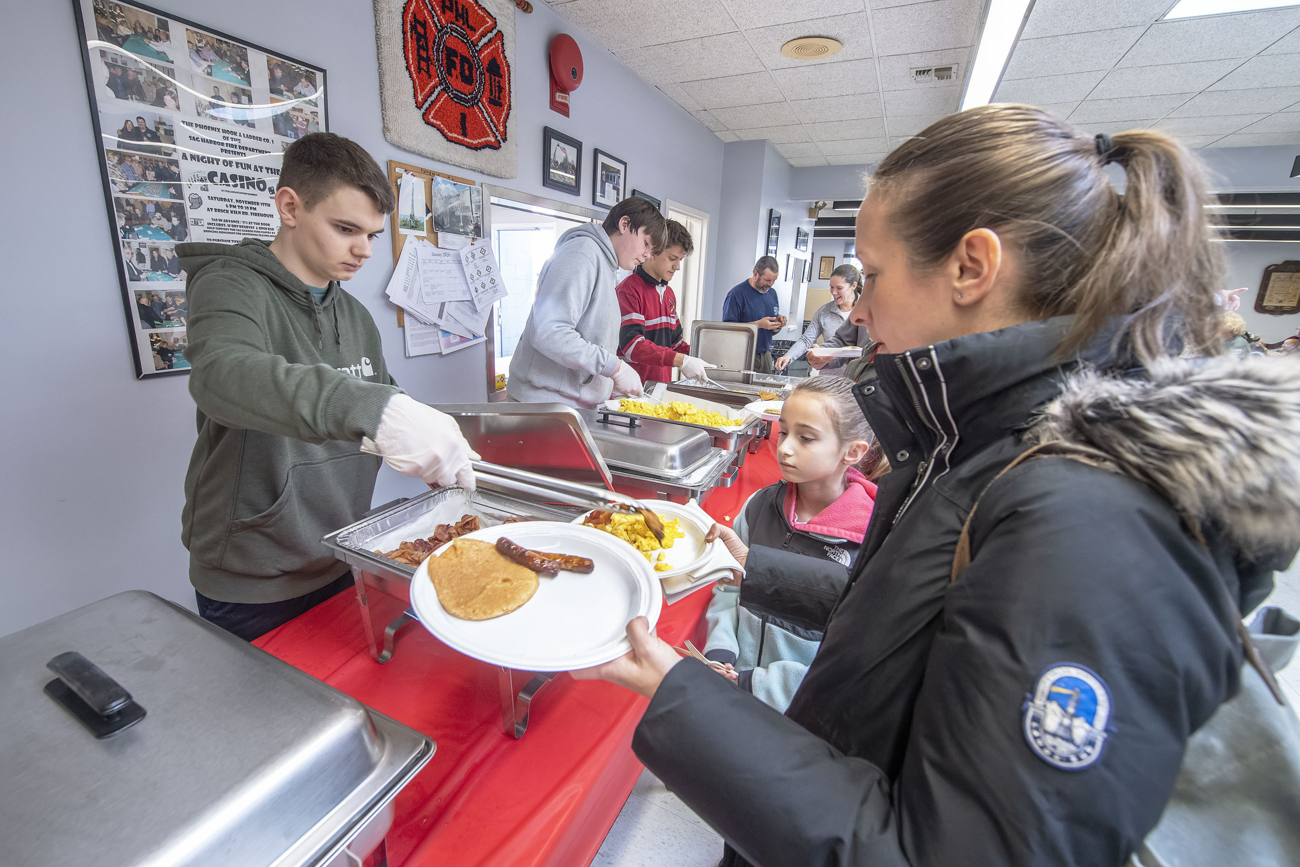 J.J. Murray serves up hash browns as his pals Colby Wilson and Truman Yardley handle the pancakes, eggs, sausage and bacon duities during the Pancake Breakfast held to benefit the Pierson Robotics Team at the Sag Harbor Fire Department firehouse on Sunday.   MICHAEL HELLER