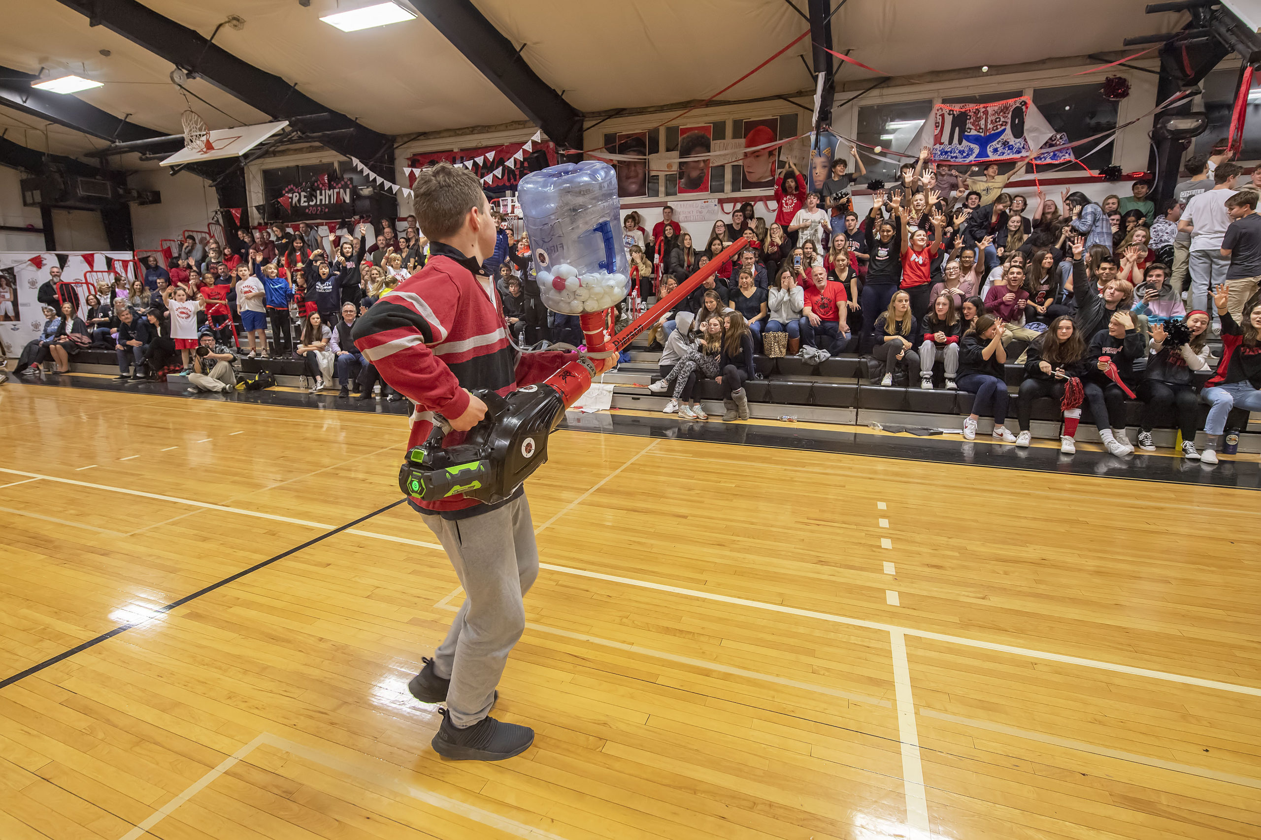 A member of the Pierson Robotics Team shoots ping pong balls into the crowd during a halftime demonstration as part of the 2020 Spirit Night festivities at Pierson High School on Friday night.