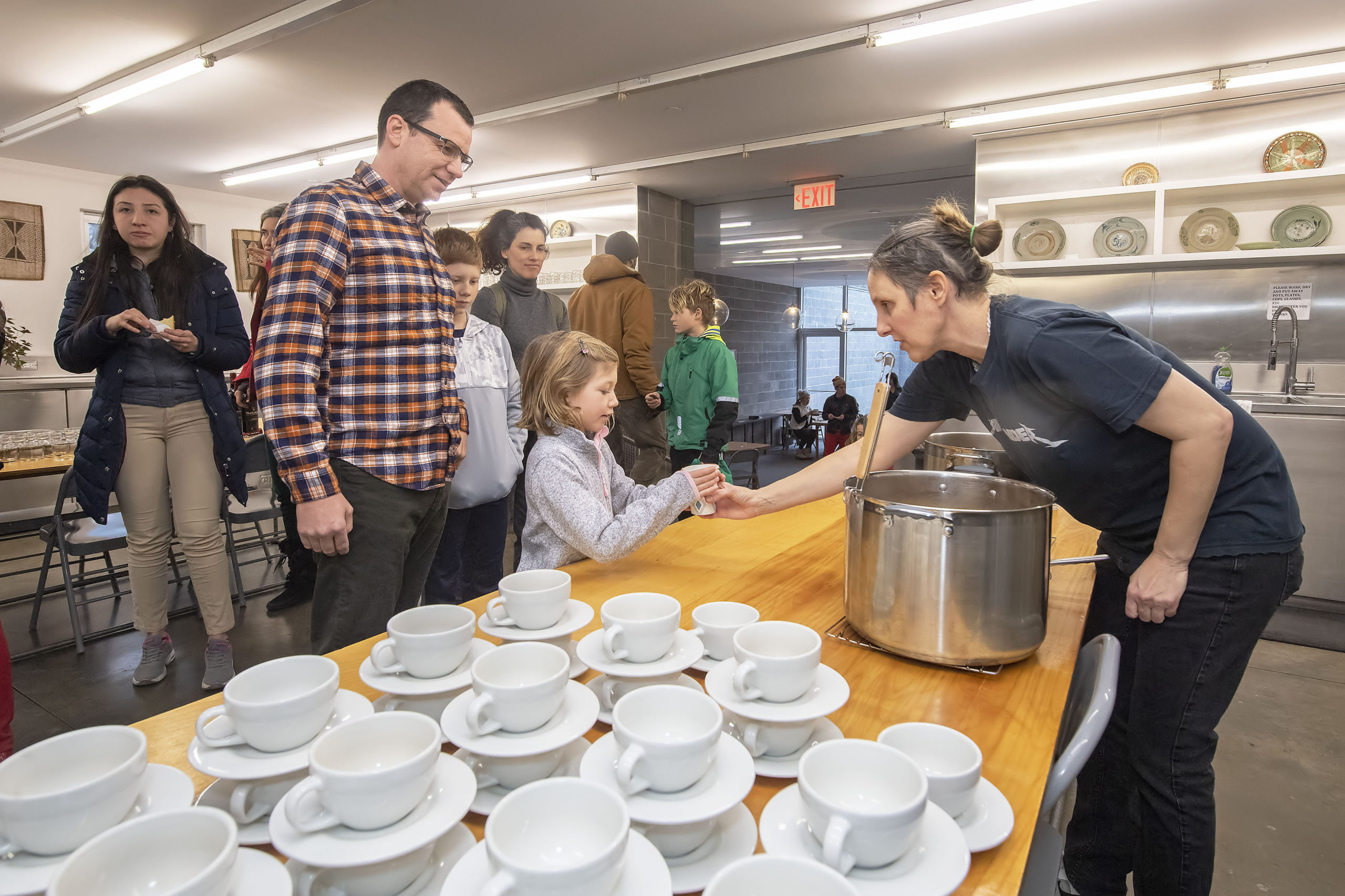 Elke Luyten hands out cups of hot mulled cider during a kickoff party at the Watermill Center on Saturday afternoon.  MICHAEL HELLER