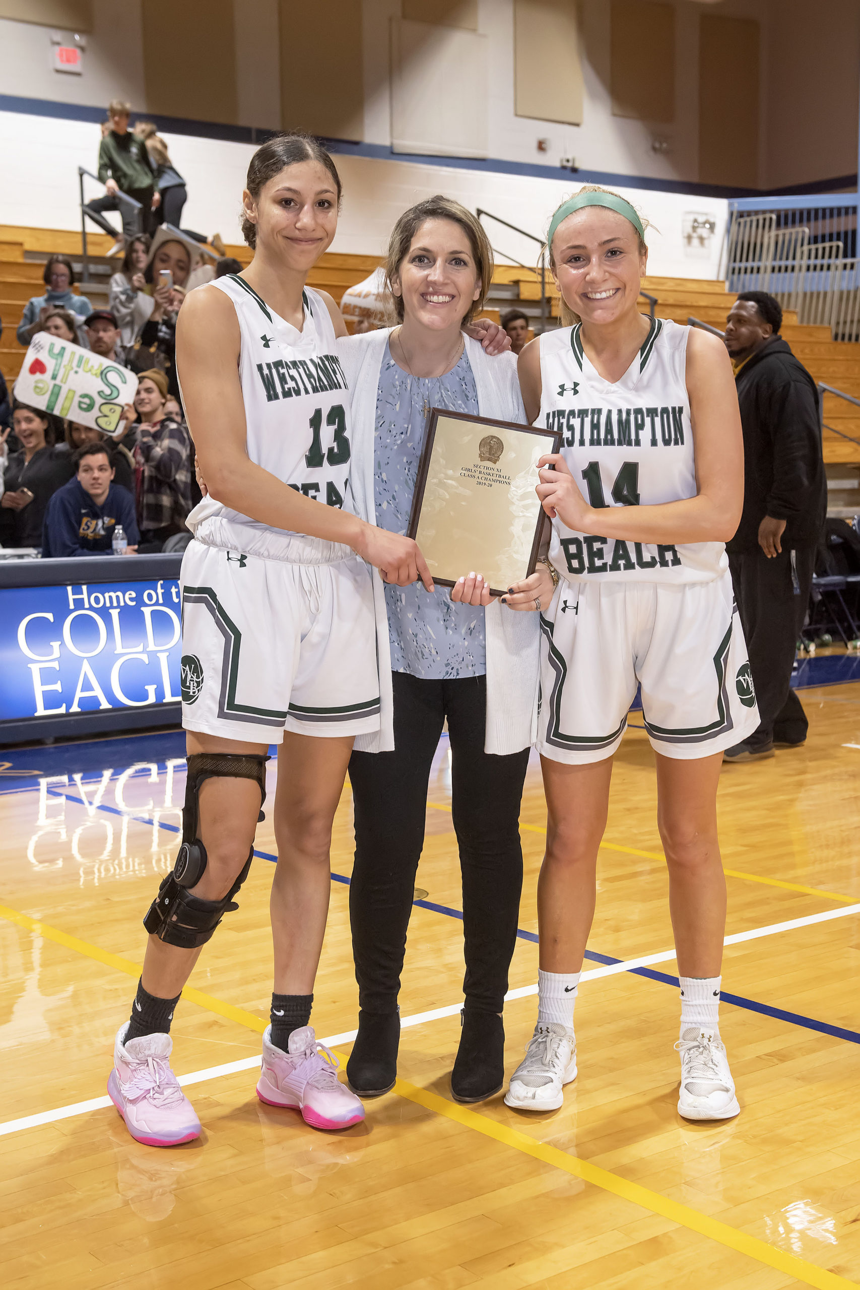 Westhampton Beach senior captains Layla Mendoza, left, and Isabelle Smith with head coach Katie Peters and the Suffolk County Class A Championship plaque.
