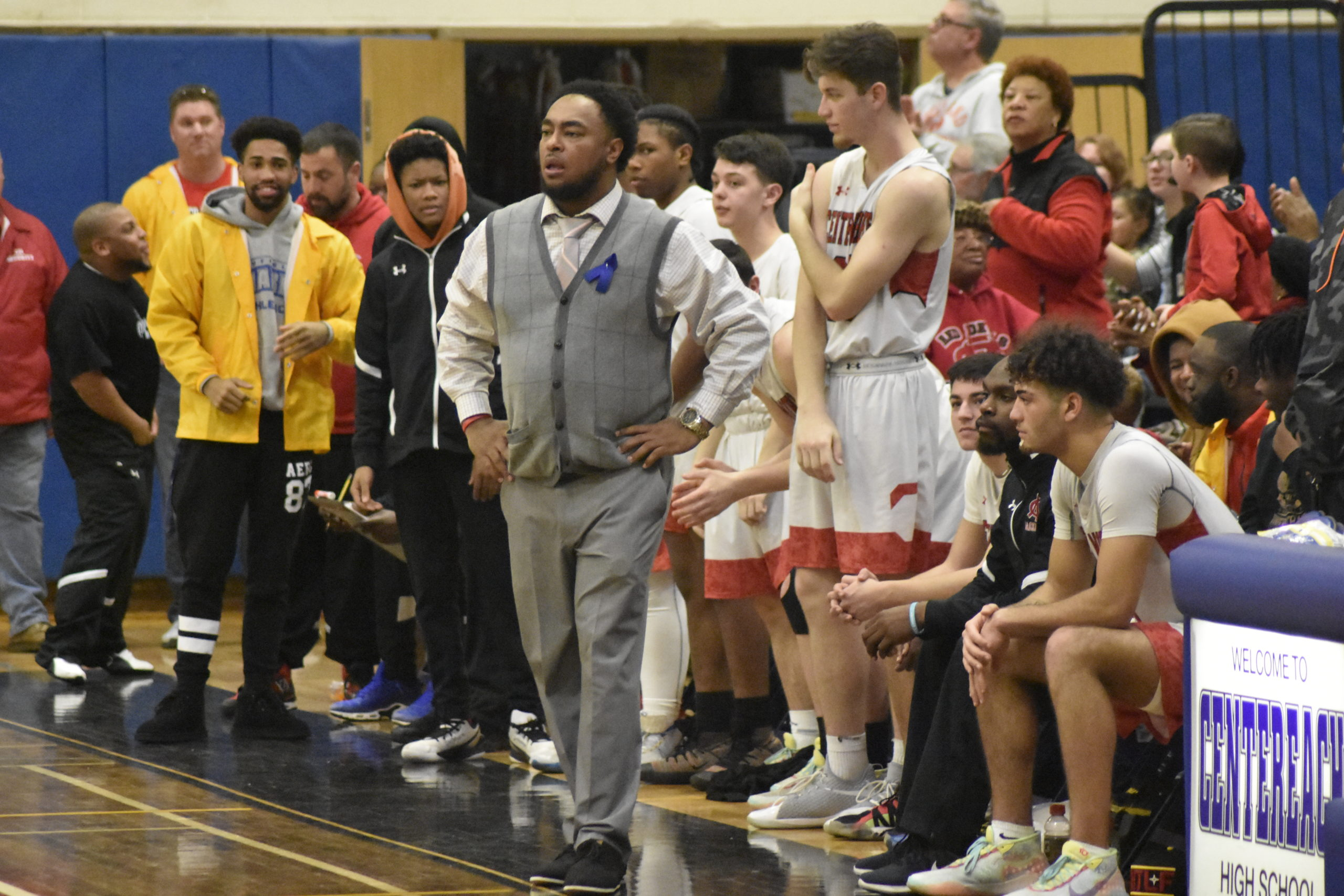Center Moriches head coach Nick Thomas with his players behind ready to celebrate their fourth consecutive county title.