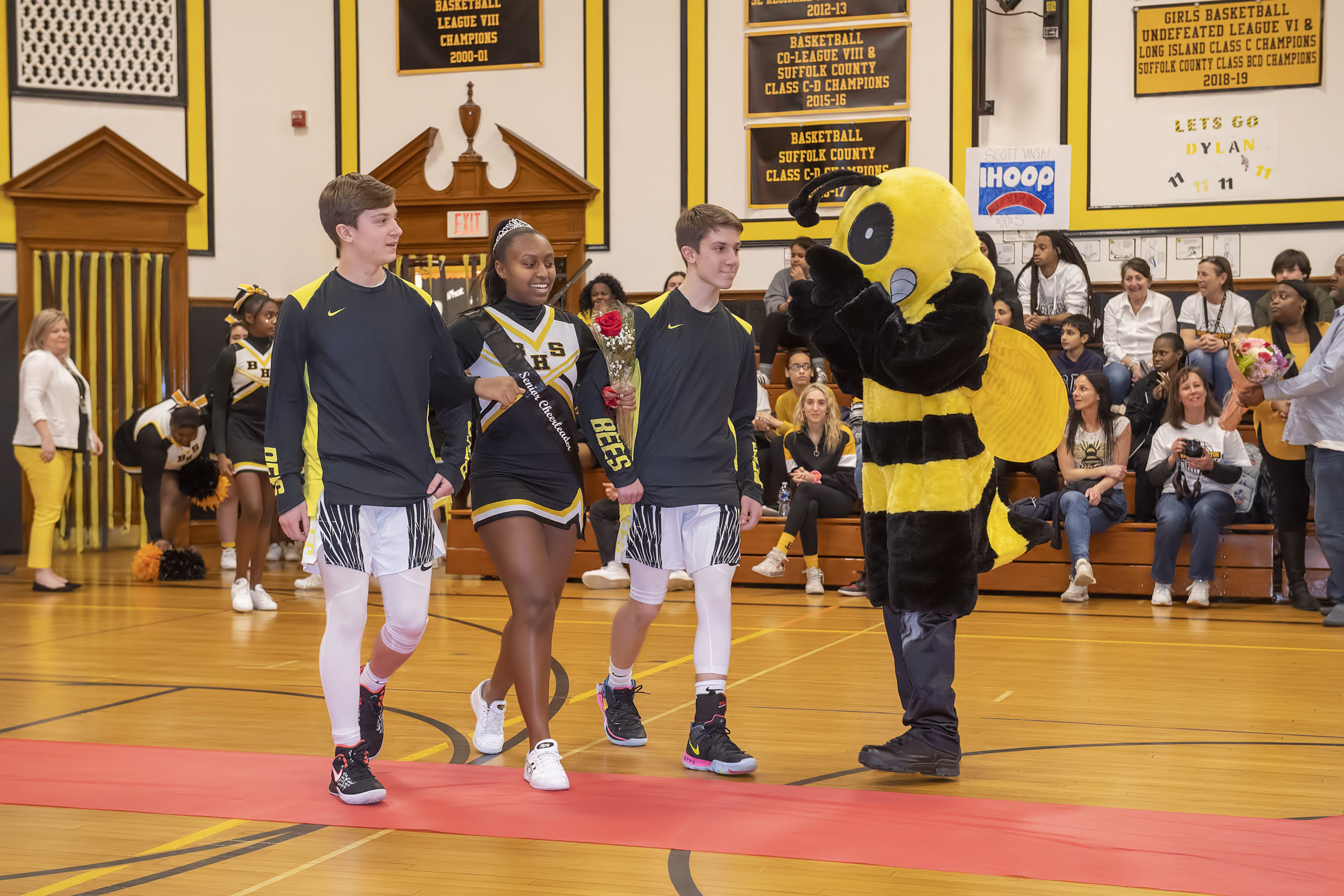 Bridgehampton School senior cheerleader Jaden Campbell is escorted onto the court by the Vinski twins, Kris and Scott. The school's senior cheerleaders were honored as part of the ceremony closing out The Beehive on February 5.