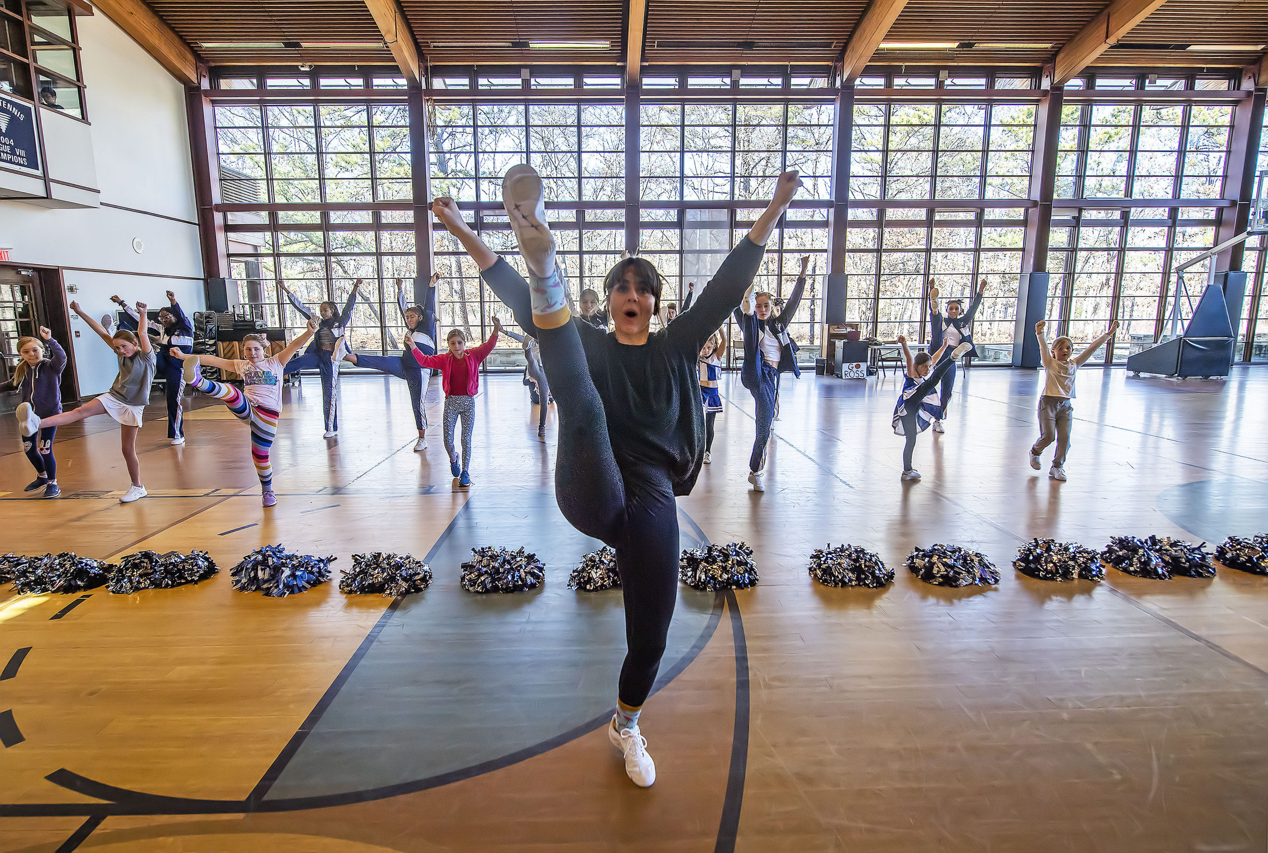 Ross School Cheerleading Coach Andrea Chesley leads a class in some beginner cheer moves during a Cheerleading Workshop that was held in the gymnasium of the Ross School on Saturday.   MICHAEL HELLER